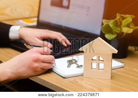 real estate buying an apartment. Real estate agent putting signing contract, sitting at the computer. moving home or renting property