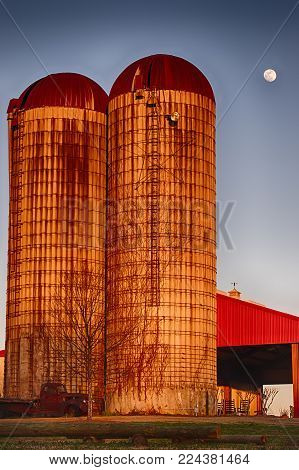 Vertial photo of two silos colored by the sunset with an old vehicle and a red roof with a bright blue sky and full moon in the background