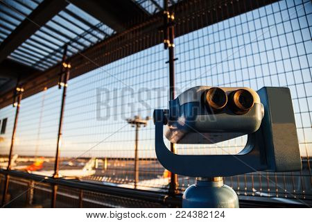 coin-operated binoculars or telescope for tourists to observe plane takeoffs and ladings in airport observation deck