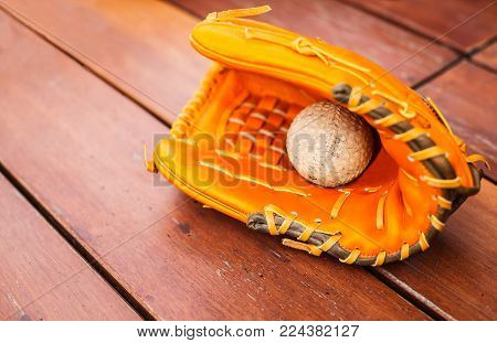 Baseball, Softball with leather mitt glove on wood table floor background with copy space. Sport Recreation Theme.