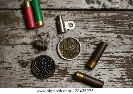 Hunting equipment. Shotgun shells hunting cartridges with gunpowder and many plumbeous fractions lead shot on wooden table background, close-up