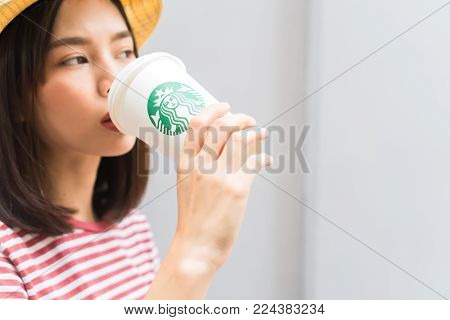 Bangkok, Thailand - January 30, 2018 : Woman drinking Starbucks coffee on the home, Starbucks brand is one of the leaders in coffee service worldwide.