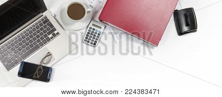 white office desk with laptop, folder, calculator, coffee, glasses and papers, business concept for finance, tax and administration, panoramic banner format, top view from above mock up with copy space