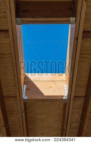 Detail of residential roof construction with framing for skylight, interior roof joists, blue sky copy space, vertical aspect
