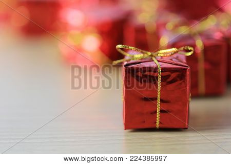 Focus in red gift box place on wooden floor and background of unsharp in the concept of festive design important.