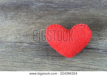 Red heart is placed on a brown wood floor and there is space available for the design of your work.