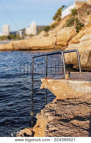 chromed iron  railing for the descent on the background of blue sea