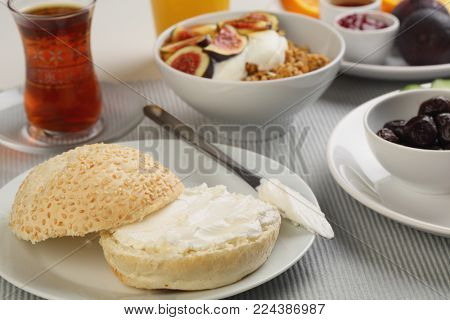 Turkish breakfast with cream cheese, vegetables, granola, fruits, and tea
