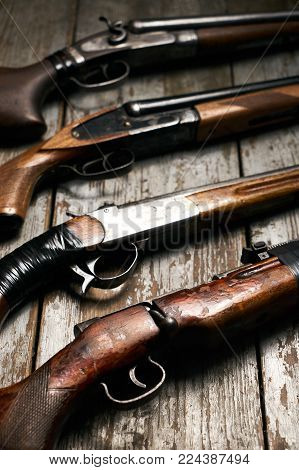 ollection of hunting rifles. Rifles, shotguns on wooden table background, Hunting guns close-up