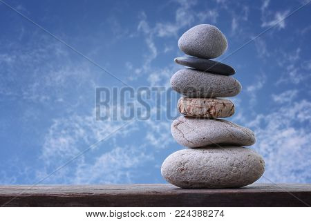 Balance Stones stacked to pyramid in the blue sky background to Spa ideas design or freedom and stability concept on rocks.
