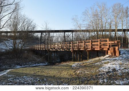 A Foot Bridge In Front Of A Railroad Trestle