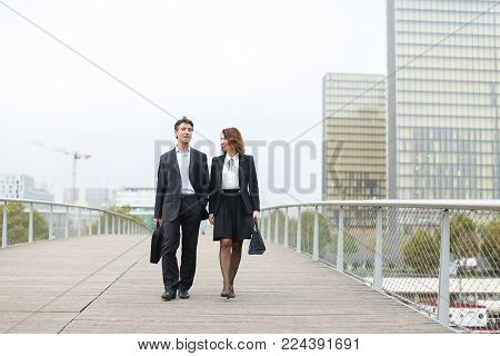 economists walk during lunch break, married American middle-aged couple going to have snack. Man and woman smiling communicating wearing strict suits. Concept of business clothes or fashionable man and woman outfits.