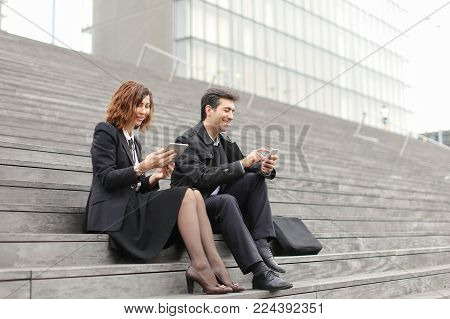 married American business couple use tablet and smartphone, middle-aged teachers planning summer holidays. Fair-haired female and male with mustache in strict outfits sitting on stairs smiling discussing travel. Concept of innovative technologies, modern