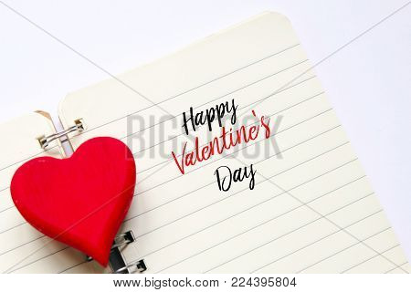 Top view of red wooden handcraft heart symbol on open book written with 'HAPPY VALENTINE'S DAY' on white  background. Valentine's day theme.