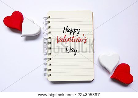Top view of red and white wooden handcraft heart symbol on open book written with 'HAPPY VALENTINE'S DAY' on white background. Valentine's day theme.