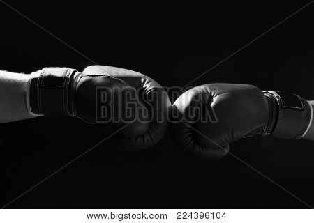 Confrontation of fighters with boxing gloves on black background