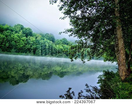Moselle River Reflecting Trees Of Water Sunset Near Toul France Campground With Mist On The River Wi