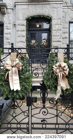 Two Gold Bows on green Christmas Wreaths adorning a black metal fence in winter holiday season. Pair of Green Wreaths.