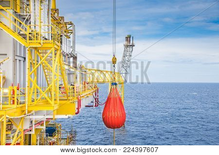 Pedestal crane annual inspection, crane pull load test activity at offshore oil and gas platform by used orange water bag simulate load.