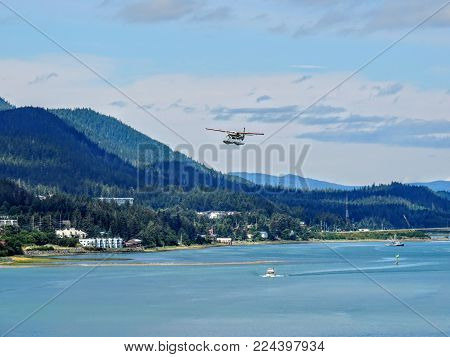 White Float Pontoon Seaplane Taking Off From Juneau Harbor With Boats And City In Background