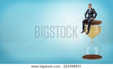 A small businessman sits with his feet hanging from a large hourglass with golden sand staring to fall down. Time management. Master of time. Schedule and planning.