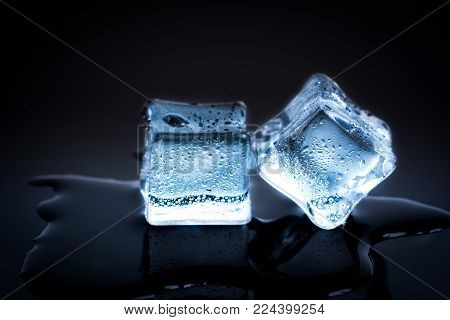 Two ice cubes on black reflection background