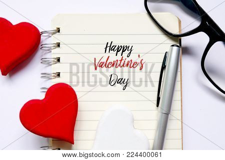 Top view of red and white wooden handcraft heart symbol on open book written with 'HAPPY VALENTINE'S DAY'  with pen and sunglass on white wooden background. Valentine's day theme.