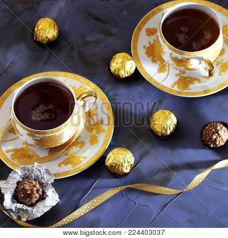 Tea ceremony, tea party. Two tea cups of gold color with black tea, candy, chocolate on a lilac color background.