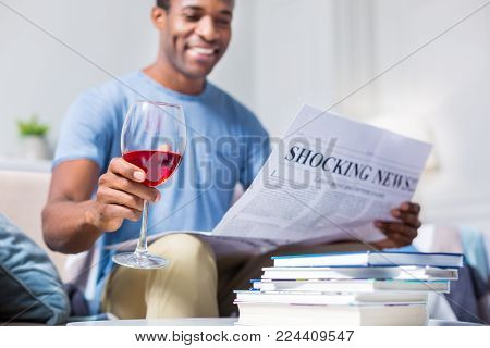Alcoholic drink. Selective focus of a glass with red wine being in hands of a cheerful nice positive man while reading a newspaper