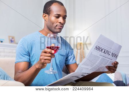 Glass of wine. Pleasant nice handsome man reading news and holding a glass of wine while drinking alcohol