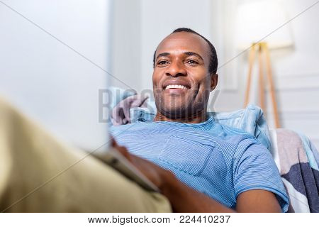 Rest at home. Joyful cheerful nice man smiling and looking at the laptop screen while resting at home