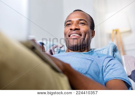 Home comfort. Joyful nice handsome man smiling and looking at the laptop screen while enjoying home comfort