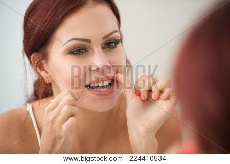 Positive young woman using dental floss while looking in mirror. Close-up of beautiful woman flossing teeth in bathroom. Dental health concept