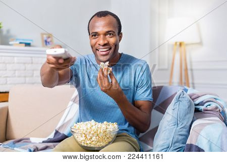 So delicious. Nice happy joyful man smiling and watching TV while holding a bowl with popcorn