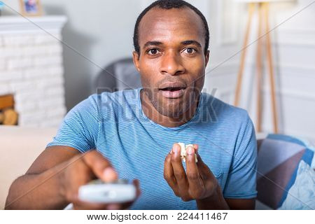 So tasty. Nice pleasant handsome man holding popcorn and eating it while watching TV program