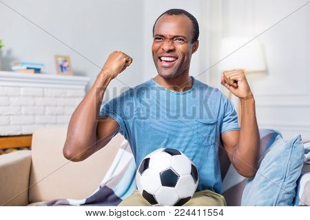 Football fan. Happy joyful nice man smiling and holding a ball while being a football fan