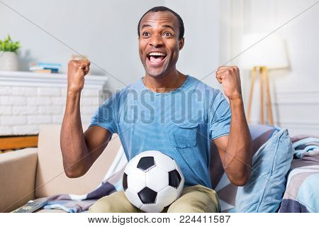 So emotional. Nice positive happy man holding a ball and expressing his happiness while being happy about his football team