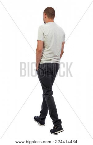 Back view of going  handsome man. walking young guy . Rear view people collection.  backside view of person.  Isolated over white background. A guy in a white T-shirt and trousers goes sideways.