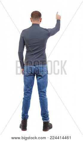 Back view of  pointing young men in  shirt and jeans. Young guy  gesture. Rear view people collection.  backside view of person.  Isolated over white background. a shortly cropped man in a dark j