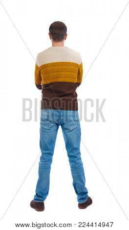 Back view of man in jeans. Standing young guy. Rear view people collection.  backside view of person.  Isolated over white background. The man put his hands behind his back in a warm sweater.