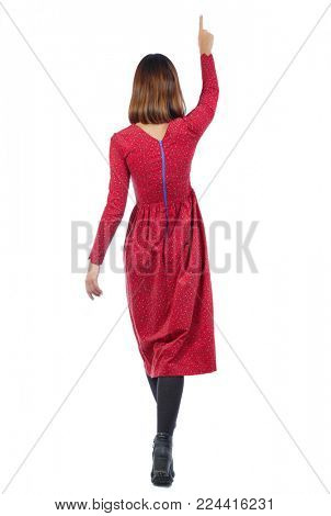 back view of pointing walking  woman. going girl pointing.  backside view of person.  Rear view people collection. Isolated over white background. A woman in a long red dress is going up