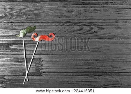 Men's mustache on a stick on a black, brutal black background. Concept: father's day, men's, male territory