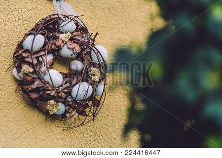 April, 17th, 2017 - Potsdam, Brandenburg, Germany. Traditional festive straw Easter wreath decorated with eggs and flowers during Easter celebration in Potsdam.