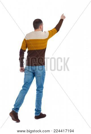 Back view of going  handsome man in jeans pointing. walking young guy . Rear view people collection.  backside view of person.  Isolated over white background. An adult man in a brown sweater sh
