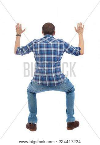 back view. man  protects hands from what is falling from above. Man holding a heavy load Rear view people collection.  backside view of person.  Isolated over white background. A man in a blue sh