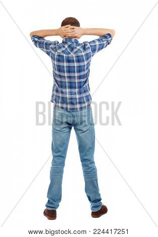 Back view of man in jeans. Standing young guy. Rear view people collection.  backside view of person.  Isolated over white background. The man in a checkered blue shirt is relaxed, laying his han