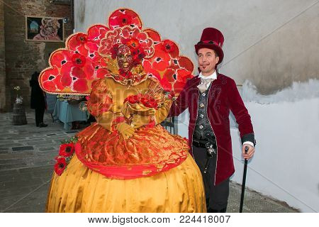 Castiglion Fibocchi, Italy - January 28, 2018: Beautiful Woman With Carnival Mask And Man With Steam