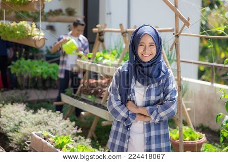 happy young asian muslim woman in rooftop garden. small urban farming