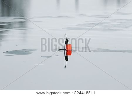 the imitation fish tackle for fishing live bait mounted on a hole on a transparent brilliant blue ice