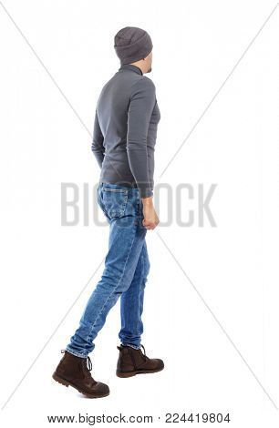 Back view of going  handsome man. walking young guy . Rear view people collection.  backside view of person.  Isolated over white background. A man in a gray sweater and a hat goes sideways